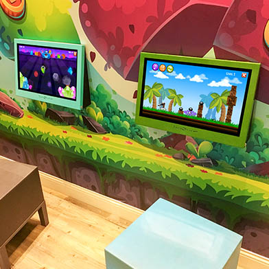 """Kidzpace 21"""" Touch2Play Max touch screen game cabinet mounted on a wall in a dental office."""